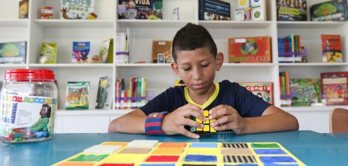 Menino, sentado em mesa, brinca com cubo mágico. Atrás dele, uma estante de livros e muitos brinquedos em volta, na mesa.