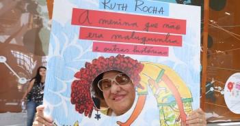 """A escritora Ruth Rocha brinca com ampliação da capa de seu livro """"A menina que não era maluquinha"""" e coloca seu rosto no lugar do rosto da menina."""