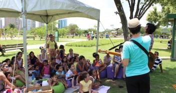 Contação de história no Parque Villa-Lobos. Um ator com violão, em pé, conversa com crianças sentadas no chão.