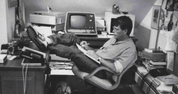 Foto do escritor Stephen King, sentado em uma cadeira, com os pés sobre a mesa e escrevendo em uma prancheta apoiada no colo.