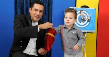 Mágico Ulisses Loddy segura um saquinho de veludo vermelho enquanto uma criança de aproximadamente 3 anos coloca a mão dentro para puxar alguma coisa.