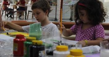 Duas crianças estão pintando. Em volta delas, na mesa, muitos potes de tinta e papéis.
