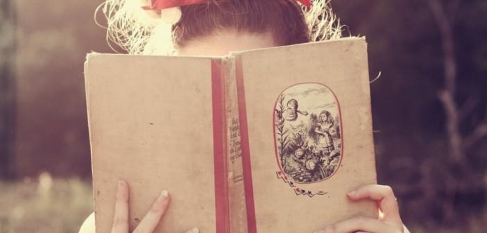 Menina loira, com laço vermelho na cabeça, lê um livro com capa bege. O livro esconde o seu rosto.
