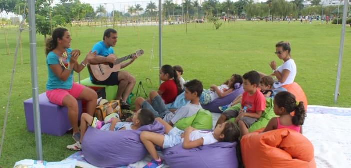 Os contadores de história Lili Fllor e Paulo Pixu cantam e tocam para frequentadores do Parque Villa-Lobos. Estão todos sentados, embaixo de uma lona.