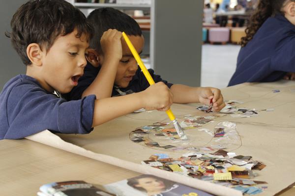 Duas crianças usam pincel com cola para colar recortes de revista.