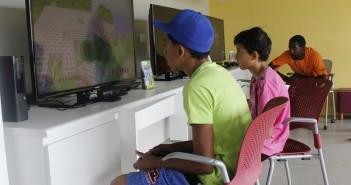 Dois garotos jogam videogame, enquanto instrutor observa.