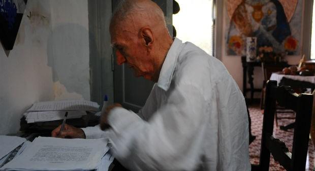 O escritor Ariano Suassuno, de perfil, em sua escrivaninha, escrevendo em folhas de papel. Ao lado dele, uma pilha de folhas.