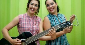 Foto da dupla de mulheres que integra a Cia. na Pona da Língua. A moça da esquerda segura um violão e a da direita, um triângulo.