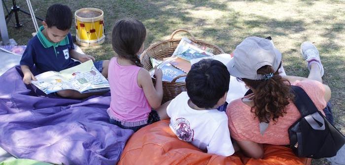 Duas crianças e uma mulher sentados em um puffs no gramado participam da atividade Domingo no Parque no Parque Villa-Lobos.