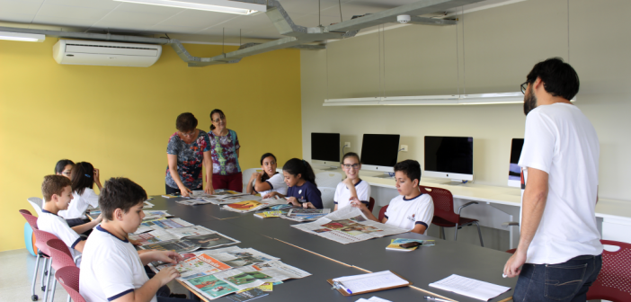 Crianças sentadas à mesa participam da oficina Espalhafatos de Texto, que produz material para o jornal Espalhafatos, que é distribuído nas bibliotecas do Estado de São Paulo