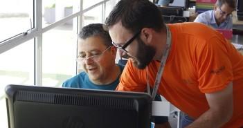 Funcionário da Biblioteca Parque Villa-Lobos, com camisa de cor laranja e crachá em volta do pescoço, ensina um aluno do Curso de Informática Básico (+60) a usar o teclado do computador. O aluno está usando um PC que fica ao lado da janela do prédio da biblioteca.
