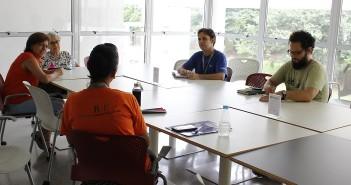 Sentados em volta de uma mesa de uma sala envidraçada da Biblioteca Parque Villa-Lobos, participantes da edição do Clube de Leitura sobre o livro 360 dias de sucesso, de Thalita Rebouças, debatem a obra